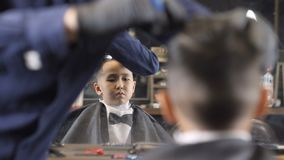 Barber in black gloves shaves the parting with a straight razor on the head of an Asian child, focus changes 60 fps. 4k stock video
