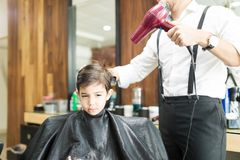 Barber Blow Drying Customer`s Hair In Shop royalty free stock photography