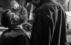 Barber busy with grooming beard of hipster client, mirror reflexion on background. Hipster with beard covered with cape. Trimming by professional barber in royalty free stock image