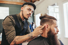 Barber checking symmetry of haircut. Of his client. Bearded men getting trendy haircut by hairstylist at barbershop Stock Image