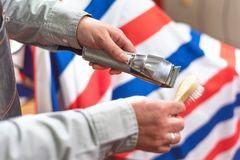 Barber cleaning electric hair clipper. Barber cleaning electric hair clipper at barber shop royalty free stock images