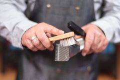 Barber cleaning electric hair clipper. Barber cleaning electric hair clipper at barber shop stock images