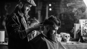 Barber with clipper trimming hair on nape of client. Barber with hair clipper works on haircut of bearded guy barbershop. Background. Hipster hairstyle concept stock photo