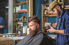 Barber with clipper trimming hair on nape of client. Hipster client getting haircut. Barber with hair clipper works on. Haircut of bearded guy barbershop stock photo