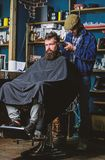 Barber with clipper trimming hair on nape of client. Hipster client getting haircut. Hipster hairstyle concept. Barber. With hair clipper works on haircut of royalty free stock photo