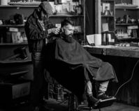 Barber with clipper trimming hair on nape of client. Hipster client getting haircut. Hipster style concept. Barber with. Hair clipper works on haircut of stock photos