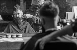 Barber with clipper trimming hair on nape of client. Reflexion of barber with hair clipper works on haircut of guy. Barbershop background. Hipster hairstyle stock photo