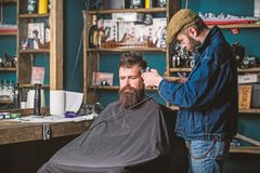 Barber with clipper trimming hair on temple of bearded client. Barber with hair clipper work on hairstyle for hipster. Barbershop background. Hipster lifestyle stock photography