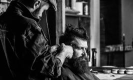 Barber with clipper trimming hair on temple of client. Hipster client getting haircut. Hipster lifestyle concept. Barber. With hair clipper works on hairstyle royalty free stock photos