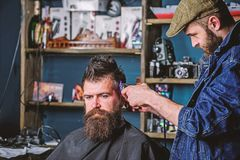 Barber with clipper trimming hair on temple of client. Hipster lifestyle concept. Hipster client getting haircut. Barber. With hair clipper works on hairstyle stock photos