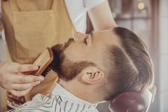 The barber combs the man`s beard with a brush. Photo in vintage style royalty free stock photo
