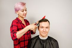 Barber cut hair, comb and shaves young man on a white background. Close up portrait of a guy and girl. Barber cut hair, comb and shaves young men on a white stock photo