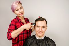 Barber cut hair, comb and shaves young man on a white background. Close up portrait of a guy and girl. Barber cut hair, comb and shaves young men on a white royalty free stock image
