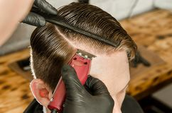 Barber cut hair and shaves the parting adult man on a brick wall background. Close up portrait of a guy. Barber cut hair and shaves the parting adult men on a stock photography