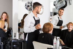 Barber cuts hair Mature woman Royalty Free Stock Image