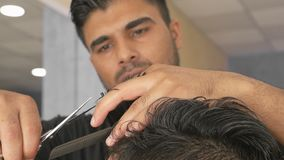 Hairdresser`s hands at the work. Barber cuts the hair by scissors at a barbershop. Attractive hairstylist makes hairstyle to the client, close-up view stock video