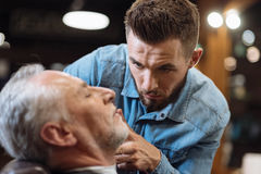 Barber cutting beard of senior client with scissors Stock Photos