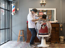 Barber cutting hair at a barber shop Stock Image