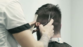 Barber cutting hair in barbershop stock video