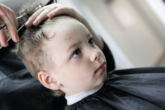 Barber cutting hair of a boy Stock Photography