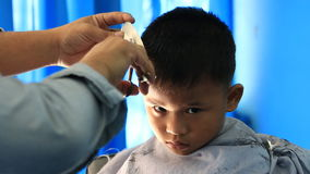 Barber cutting hair for boy. stock video