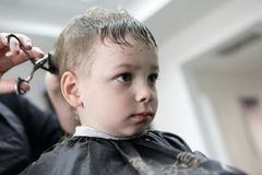 Barber cutting hair of a child Stock Image