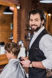 Barber cutting hair of little kid with Hair Clipper and looking. At camera royalty free stock images