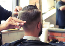 Barber cutting hair with scissors stock photos