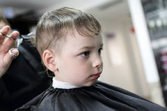 Barber cutting hair of a serious child Royalty Free Stock Photos
