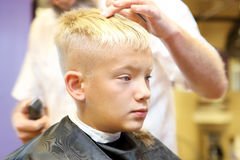 Barber cutting hair of young boy Royalty Free Stock Photography