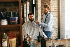 Barber Cutting Man Beard In Barber Shop Skägghårsnitt arkivbilder