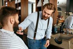 Barber Cutting Man Beard In Barber Shop Skägghårsnitt royaltyfri foto