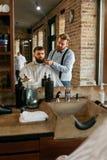 Barber Cutting Man Beard In Barber Shop Skägghårsnitt royaltyfria foton