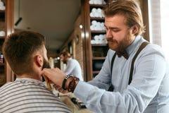 Barber Cutting Man Beard In Barber Shop Skägghårsnitt arkivbild