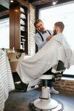 Barber Cutting Man Beard In Barber Shop Taglio dei capelli della barba immagine stock libera da diritti