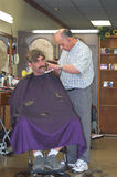 Barber cutting man's hair. Old fashioned barber shop - man getting his hair cut in a barber shop Stock Images