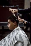The barber is cutting a man`s hair holding scissors and comb in his hands opposite the mirror in a barbershop royalty free stock images