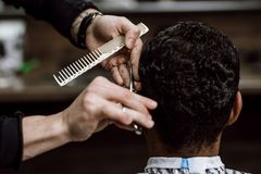 The barber is cutting a man`s hair holding scissors and comb in his hands opposite the mirror in a barbershop royalty free stock photography