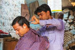 Barber cutting man`s hair at the street market in Fatehpur Sikri Royalty Free Stock Photography