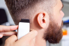 Barber cutting and modeling hair by electric trimmer royalty free stock photography