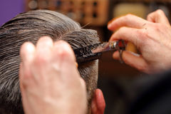 Barber cutting and modeling hair by scissors and comb Royalty Free Stock Image