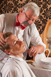 Barber cutting mustache Stock Photography