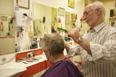 Barber cutting senior man's hair in barbershop Stock Image