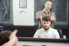 Barber discusses haircut with client Royalty Free Stock Photo