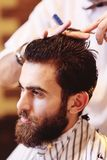 Barber does a haircut for a young handsome man with a beard and mustache Royalty Free Stock Photos