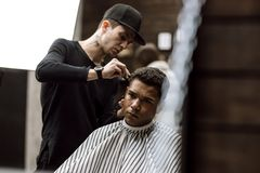 The barber dressed in black clothes makes a razor cut hair back and sides for a stylish man sitting in the armchair in a stock photography