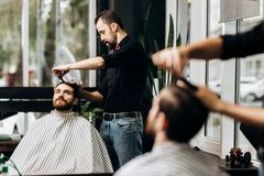 Barber dressed in a black shirt with a red bow tie scissors the man`s hair in a barbershop stock photography