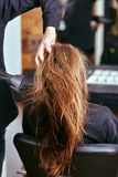Barber dries the hair with the hair dryer of young, beautiful girl in a beauty salon Royalty Free Stock Images