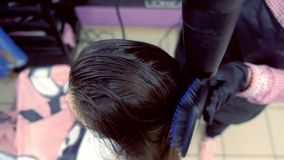 Barber drying hair with hair dryer. Strengthening the hair with keratin. stock video footage