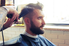 Barber with electric clipper and comb Royalty Free Stock Photos